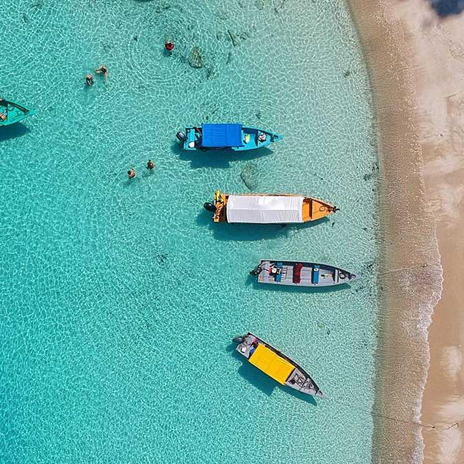 Bunte Boote an einem Strand mit türkisblauem Wasser