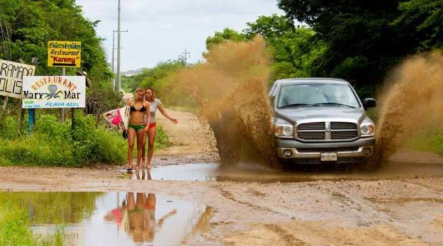 Zwei Frauen mit Surfbrett laufen auf Erde und Auto fährt vorbei