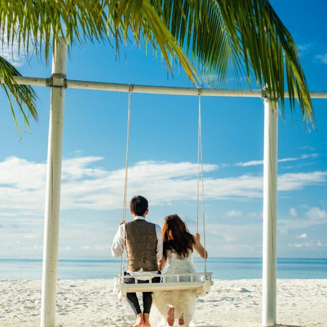 Brautpaar auf Schaukel am Strand